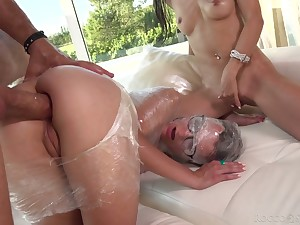 Plastic wrap porn scene featuring two nerdy girls in glasses